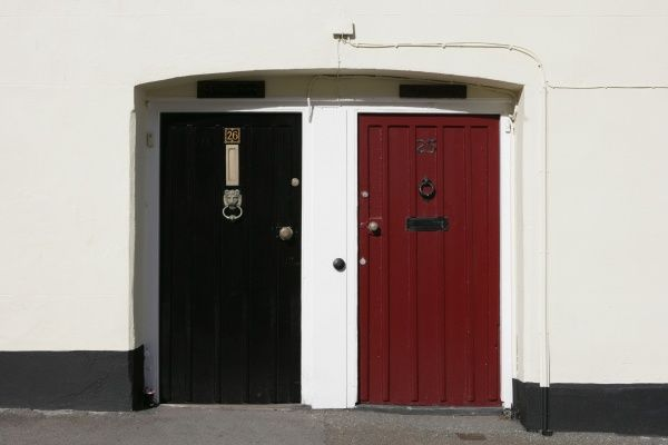 A pair of front doors painted red and black with the white walls of houses number 24 and 25 in a village on the Rames Head Cornwall on the South Coast of England