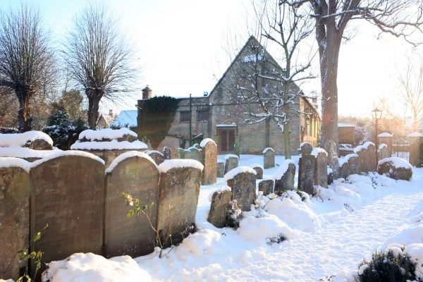 The church yard covered in snow on cold winters day at the cotswold town of Burford Oxfordshire