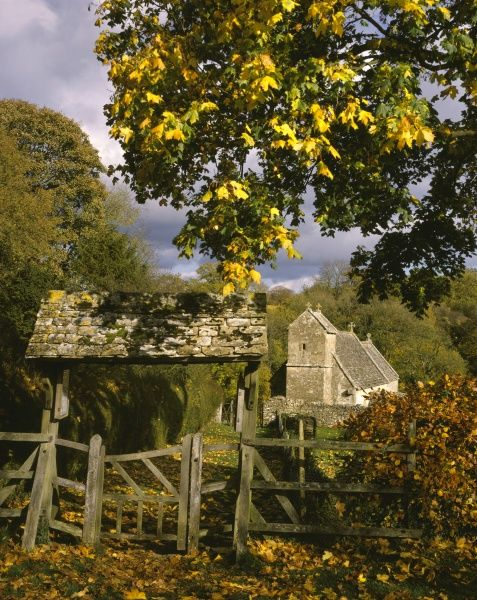 A cotswold church with its Gate in the cotswold village of Duntisbourne Rouse Gloucestershire on a autum day