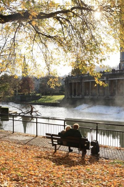 Two lovers on a sunny morning in early winter beside the River Avon in the City of Bath with the leaves around there park bench