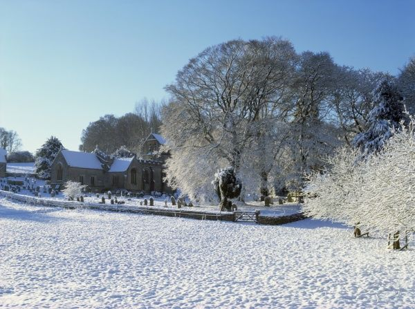 The Cotswold village of North Cerney with its fine church on a winters morning after a fall of snow