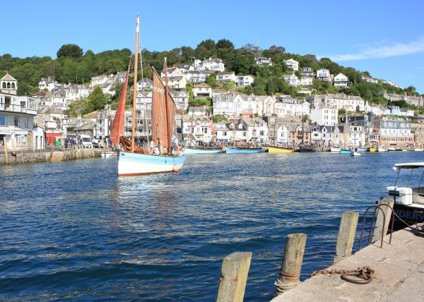 The picturesque fishing village of Looe on the south coast of Cornwall as a traditional lugger sails out of the harbour